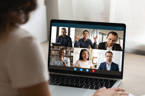 A person is partially obscured and is looking at the computer screen of six people in an online video meeting